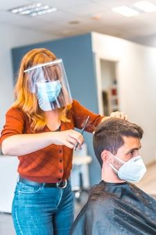 コロナウイルス大流行後の美容院。フェイスマスクと保護スクリーンを備えた美容師、covid-19。社会的距離、新しい正常性。スペインで若い白人男性をハサミで切る