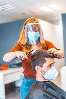 コロナウイルス大流行後の美容院。フェイスマスクと保護スクリーンを備えた美容師、covid-19。社会的距離、新しい正常性。ハサミで若い白人男性を切る