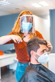 コロナウイルス大流行後の美容院。顔のマスクと防護スクリーンを備えた白人美容師、covid-19。社会的距離、新しい正常性。若い白人男性にハサミで髪を切る