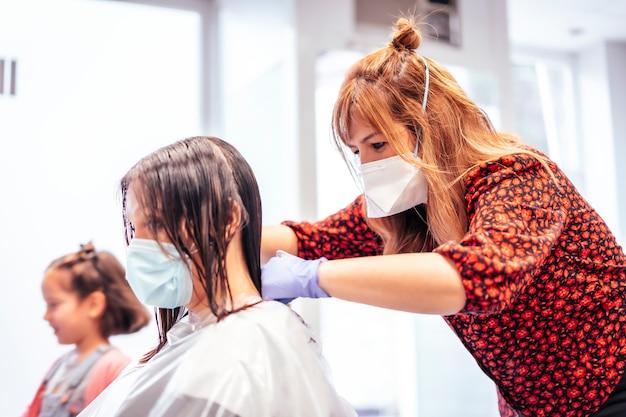 クライアントをカットするマスクと手袋を備えた美容師とクライアントの娘が翼のある演奏をします。 covid-19パンデミックにおける美容院のセキュリティ対策を再開