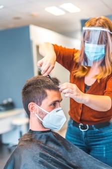コロナウイルス大流行後の美容院。顔のマスクと防護スクリーンを備えた白人美容師、covid-19。社会的距離、新しい正常性。ハサミで若いブルネットに髪を切る