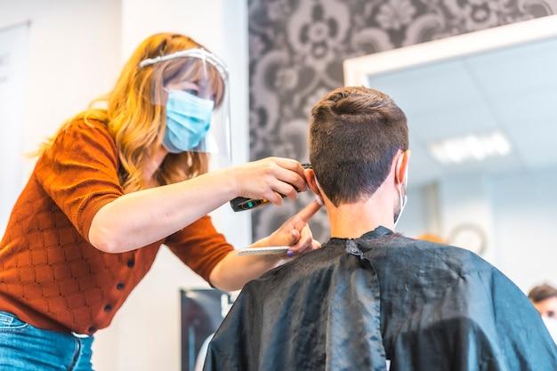 コロナウイルスの流行後の美容院のオープン、covid-19。セキュリティ対策、フェイスマスク、防護スクリーン、社会的距離。若いブルネットを扱う金髪白人美容院