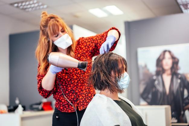 ヘアドライヤーでクライアントの髪を乾燥させるマスクと手袋を備えた美容院。 covid-19パンデミックにおける美容院のセキュリティ対策を再開