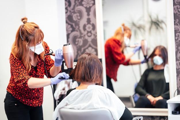 クライアントドライヤーの髪を滑らかにするマスクと手袋の美容師。 covid-19パンデミックにおける美容院のセキュリティ対策を再開