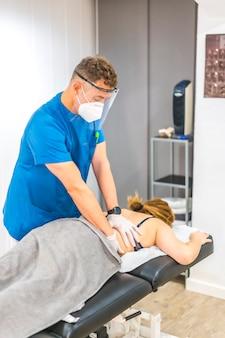 画面とマスクが患者の背中を操作する理学療法士。 covid-19パンデミックにおける理学療法の安全対策を再開します。オステオパシー、治療用キロマッサージ