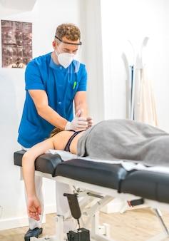 ストレッチャーで患者と一緒に働くスクリーンとマスクを持つ理学療法士。 covid-19パンデミックにおける理学療法の安全対策を再開します。オステオパシー、治療用キロマッサージ