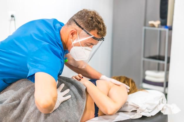 画面とマスクで若い女性にヒップマッサージを与える理学療法士。 covid-19パンデミックにおける理学療法の安全対策を再開します。オステオパシー、治療用キロマッサージ