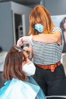 クライアントに暗い色合いを与えるフェイスマスクを持つ白人の美容院。 covid-19パンデミックにおける美容院の安全対策。新しい正常、コロナウイルス、社会的距離