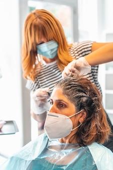 美容院でクライアントに暗い色合いを与えるフェイスマスクとブロンドの美容院。 covid-19パンデミックにおける美容院の安全対策。新しい正常、コロナウイルス、社会的距離