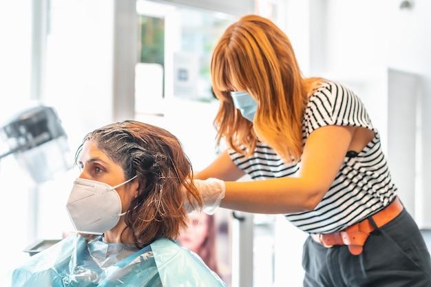 美容師がクライアントに暗い色合いを与えるフェイスマスクのある美容師。 covid-19パンデミックにおける美容院の安全対策。新しい正常、コロナウイルス、社会的距離