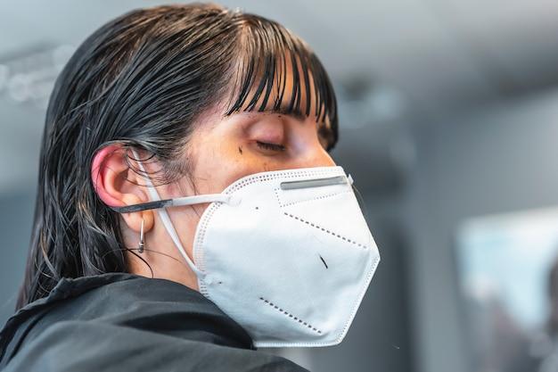 ヘアサロンでマスクを持つ若いブルネットの少女。 covid-19パンデミックにおける美容院のセキュリティ対策を再開。新しい正常、コロナウイルス、社会的距離