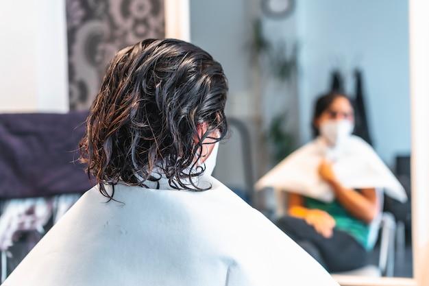 鏡を見てフェイスマスクを持つクライアント。 covid-19パンデミックにおける美容院の安全対策。新しい正常、コロナウイルス、社会的距離