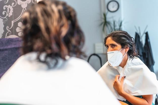 フェイスマスクを装着したクライアントは、色合いが鏡でどのように見えるかを確認します。 covid-19パンデミックにおける美容院の安全対策。新しい正常、コロナウイルス、社会的距離