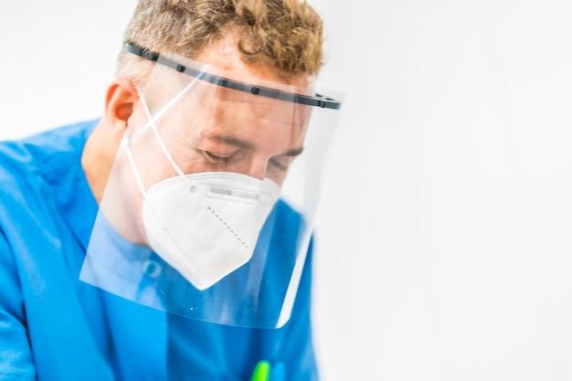 理学療法士がプラスチック製のスクリーンとマスクを操作します。 covid-19パンデミックにおける理学療法の安全対策を再開します。オステオパシー、治療用キロマッサージ