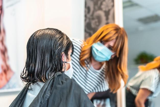 クライアントに髪をカットするフェイスマスクの美容師。 covid-19パンデミックにおける美容院の安全対策。新しい正常、コロナウイルス、社会的距離