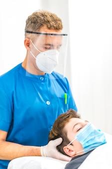 子供に頭蓋マッサージを与えるマスクと画面を持つ理学療法士。 covid-19パンデミックにおける理学療法の安全対策を再開します。オステオパシー、治療用キロマッサージ