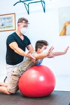 マスクと背中をしている画面を持つ理学療法士は子供にストレッチします。 covid-19パンデミックにおける理学療法士のセキュリティ対策を開始します。オステオパシー、治療用キロマッサージ