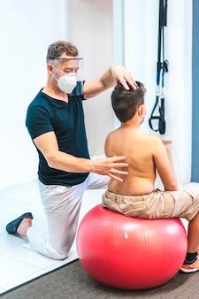 マスクと子供の背中を見て画面を持つ理学療法士。 covid-19パンデミックにおける理学療法士のセキュリティ対策を再開。オステオパシー、治療用キロマッサージ