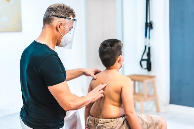 マスクと子供にマッサージをしている防護スクリーンを持つ理学療法士。 covid-19パンデミックにおける理学療法士のセキュリティ対策を再開。オステオパシー、治療用キロマッサージ