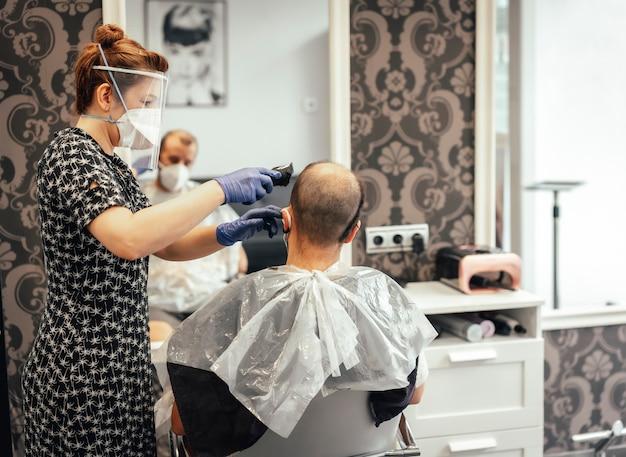 Covid-19、新しい正常性、社会的距離、保護マスクで髪をカットするためのセキュリティ対策を備えた美容師