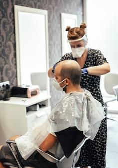 Covid-19、新しい正常性、社会的距離、美容師、マスクを備えたクライアントのためのセキュリティ対策を備えた美容師。短いショートヘアをカット