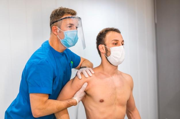 スクリーンとマスクで肩のマッサージをする理学療法士。コロナウイルスのパンデミック、covid-19の保護対策を伴う理学療法。オステオパシー、治療用キロマッサージ