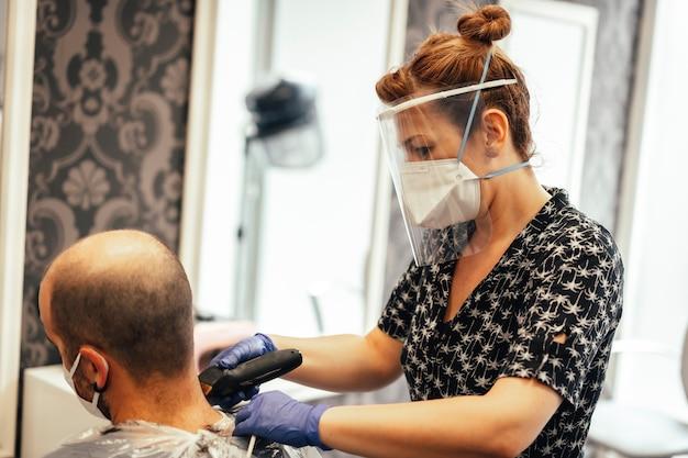 Covid-19、新しい正常性、社会的距離、美容師、マスクを備えたクライアントのためのセキュリティ対策を備えた美容師。刃で切る