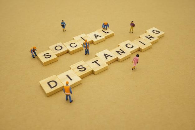 Социальное дистанцирование. миниатюрные люди остаются в стороне, чтобы уменьшить вирусную инфекцию covid 19. поддерживать социальную дистанцию