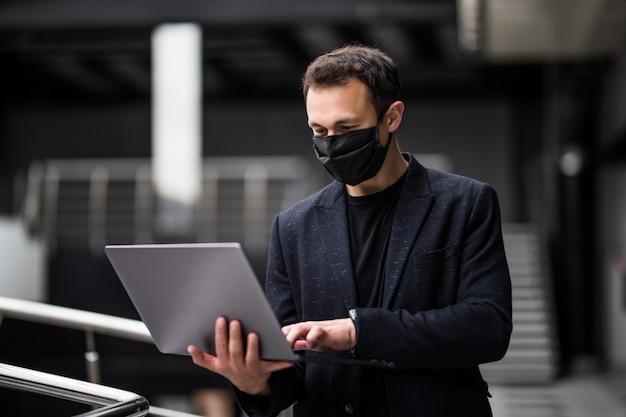 Карантинное общение. бизнесмен в медицинской маске работая на компьтер-книжке на офисе. коронавирус. covid-19. остаться дома