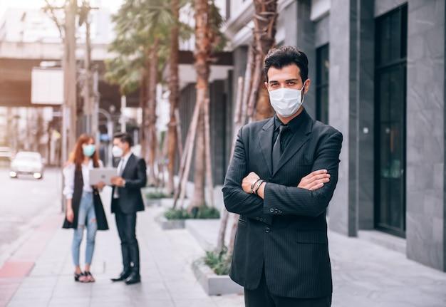 ビジネス地区に立っているハンサムな実業家と彼はコロナウイルスcovid-19発生状況の中での新しいビジネスプロジェクトに自信を持っています。ヘルスケアとビジネスのコンセプト