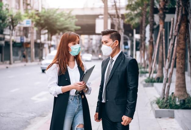 新しいビジネスのために屋外の場所で働いて調査しているアジアのビジネス人々は、インフルエンザとコロナウイルスcovid-19の発生を防ぐために保護マスクを着用しています。ヘルスケアとビジネスのコンセプト