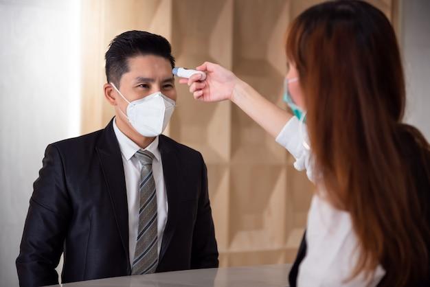 Оператор проверяет лихорадку у посетителя цифрового термометра на счетчике информации для сканирования и защиты от коронавируса covid-19