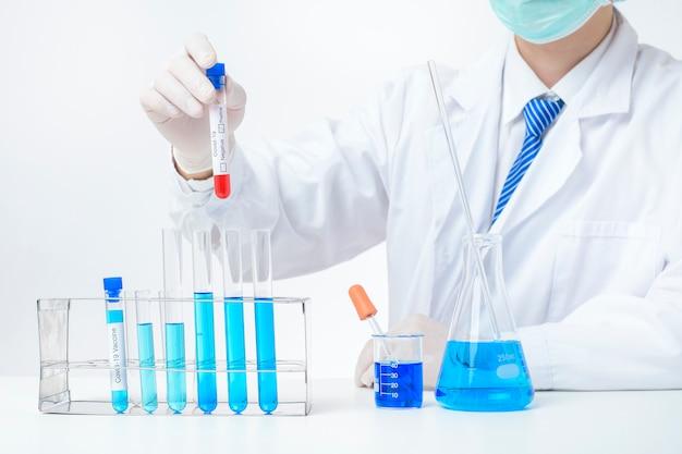 実験室のアシスタントの手が血液検査に感染したcovid-19を持っている