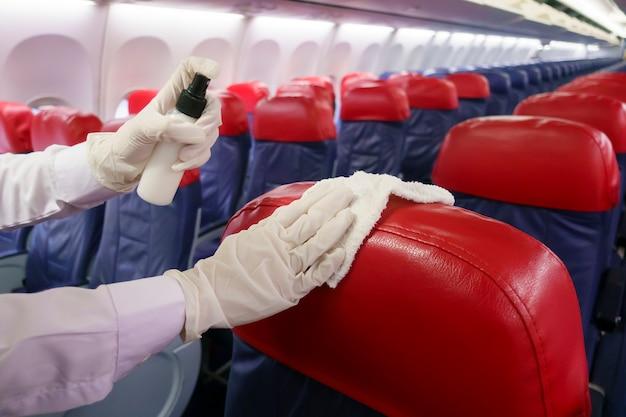 クローズアップの手はcovid-19防止パンデミックのための航空機の座席を掃除する手袋を着用しています。