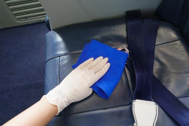 クローズアップ手はcovid-19予防のパンデミックのため航空機を掃除する手袋を着用しています。