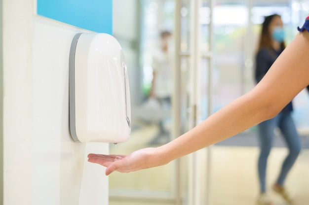 女性の手を閉じるはショッピングセンター、covid-19保護概念でアルコールゲルを使用しています