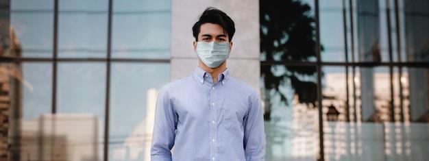 Covid-19ビジネスコンセプトの状況。都市に立っているサージカルマスクを持ったビジネスマン
