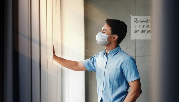 Covid-19コンセプトのための自宅検疫。家の窓際に立っているサージカルマスクを持つ若者。