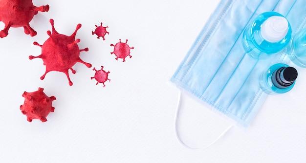Коронавирус (covid-19), построенный методом лепки из глины с акварельной росписью, имеет хирургические маски и дезинфицирующий гель для рук для защиты от гигиенического распространения на белом