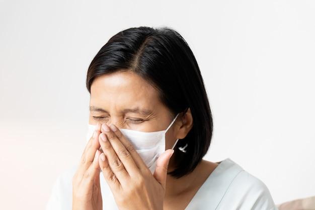 Женщина чихает под маской, прикрывая рот и нос во время кашля. корона вирус или концепция covid-19.