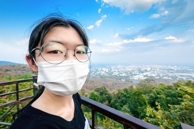チェンマイ市の山のビューポイントで外科医療マスクの顔の保護を身に着けている女性、covid-19の概念を防ぐ