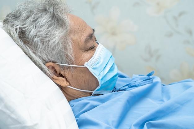 Азиатский старший пациент женщины нося лицевой щиток гермошлема в больнице для защищает вирус covid-19.