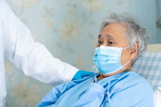 Доктор касаясь азиатскому старшему пациенту женщины нося лицевой щиток гермошлема в больнице для защищает вирус covid-19.