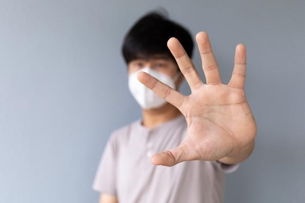 手のひらを見せてコロナウイルス(covid-19)を保護するマスクを身に着けている男性のクローズアップ