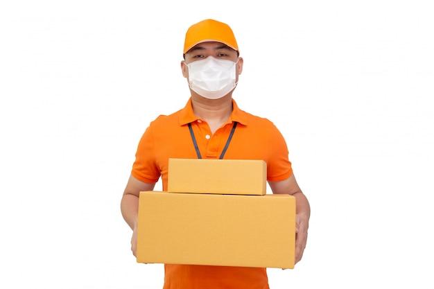 Работник службы доставки держит коробку с посылкой и носит защитную маску для предотвращения вируса covid-19, изолированного на белой стене, доставку через интернет и концепцию быстрой экспресс-доставки