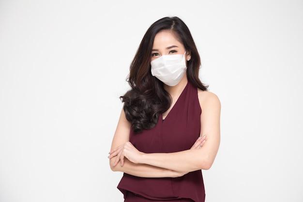 白い壁に分離されたウイルスcovid-19を防ぐために腕を組んで防護医療マスクを身に着けている赤いドレスを着たアジアのビジネスウーマンの肖像画