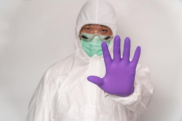 防護服とマスクを着た医師が、自宅での滞在によりコロナウイルス(covid-19)の発生を阻止するためのストップジェスチャーを示している