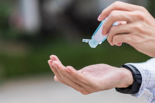 Мужские руки, используя дезинфицирующий гель для мытья рук, против нового коронавируса или коронирусной болезни (covid-19)