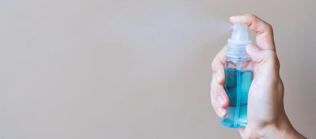 公共の屋外で小説のコロナウイルスまたはコロナウイルス病(covid-19)に対するアルコール消毒剤ボトルディスペンサーを噴霧する女性の手。防腐剤、衛生、ヘルスケアのコンセプト