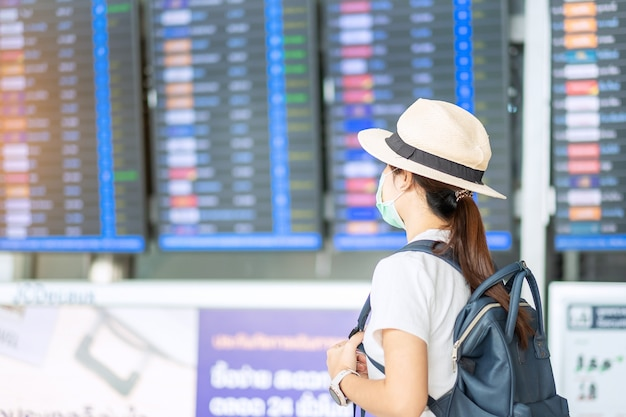 空港ターミナルでサージカルマスクを身に着けている若い成人女性、保護コロナウイルス病(covid-19)感染症、アジアの女性旅行者の帽子で旅行の準備ができています。新しいノーマルとトラベルバブルのコンセプト
